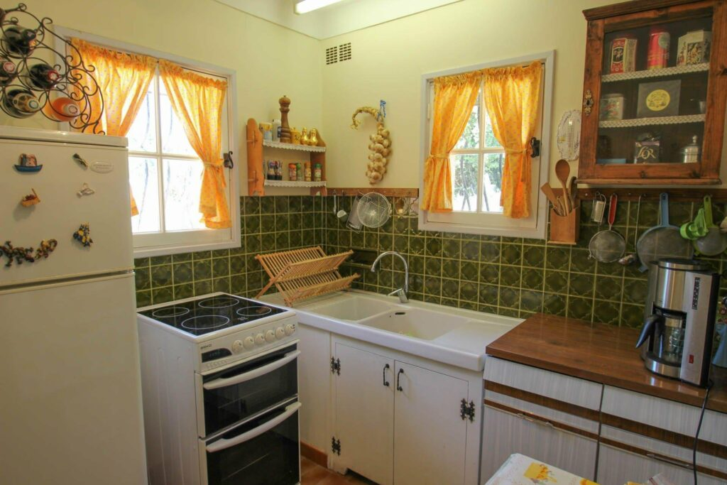kitchen in countryside house with green tiling and white appliances