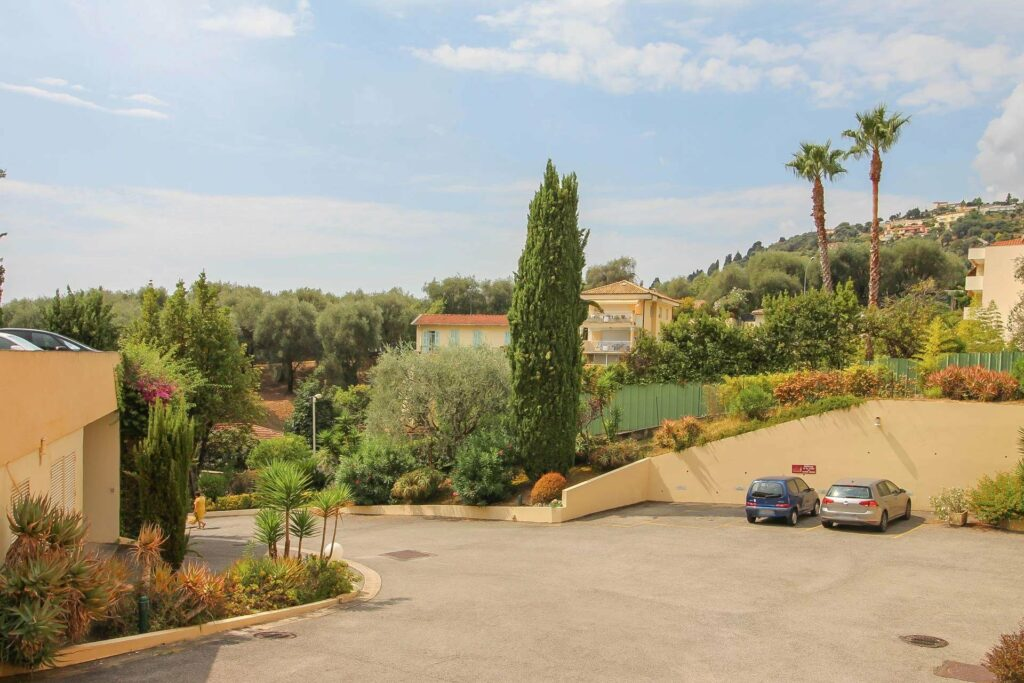 driveway of apartment for sale in menton with green tree and plants