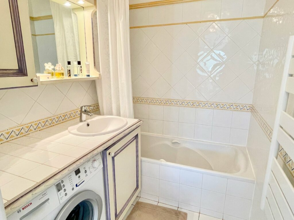 bathroom with white bathtub and counter tops and bath tub