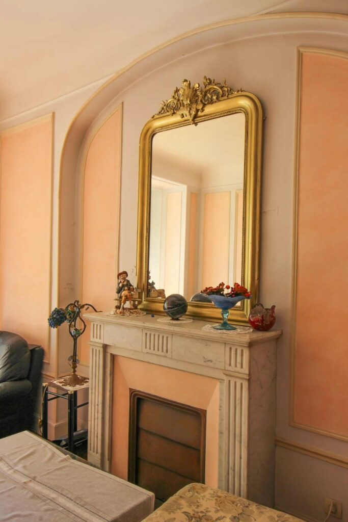 fire place with gold mirror above in living room