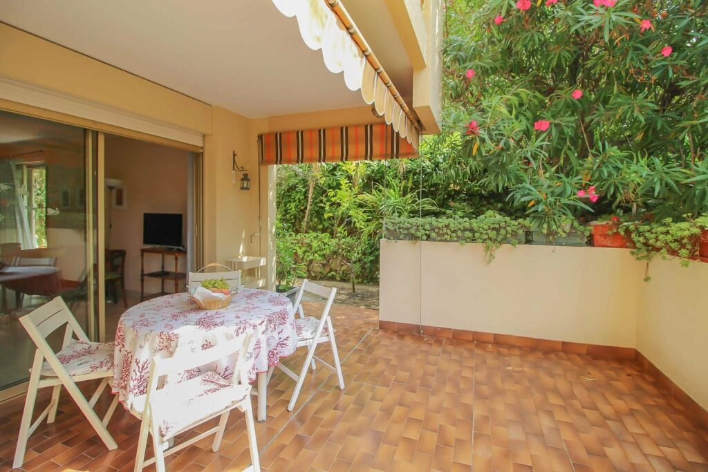 terrace with white table and stone tile floors in menton apartment