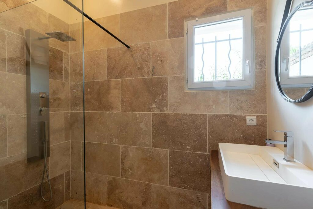 bathroom with stone tile walls and small window
