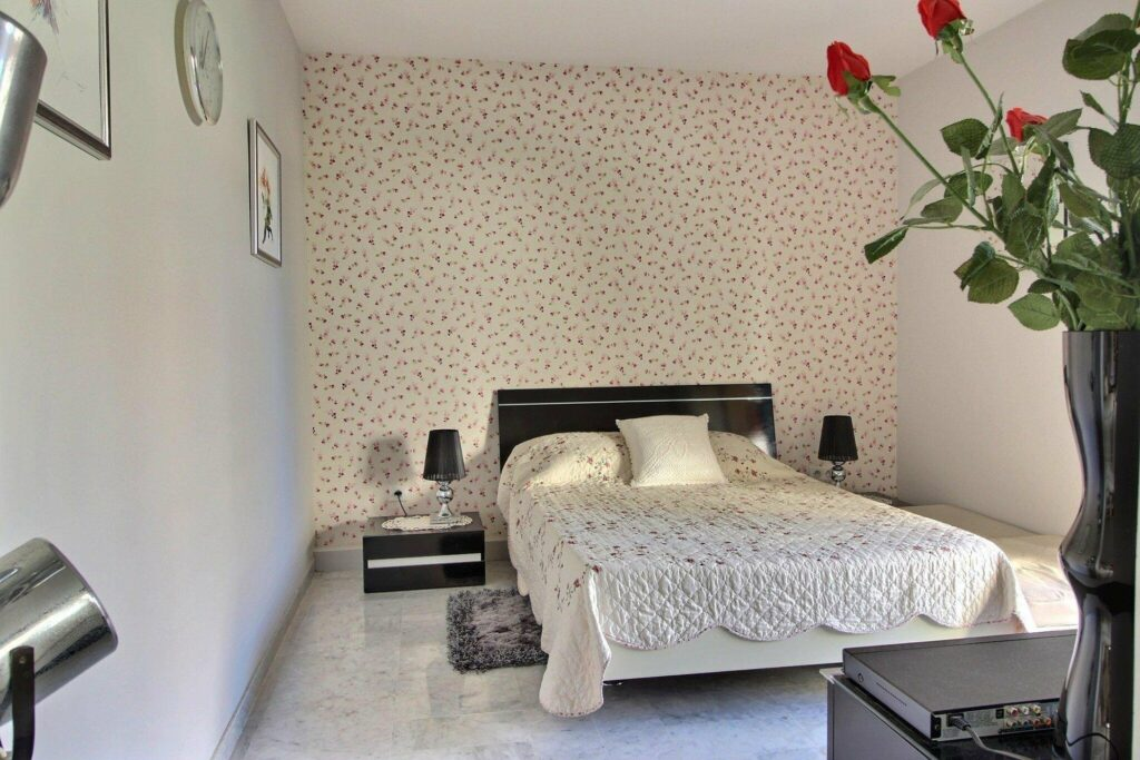 bedroom with floral wallpaper and floral bedding