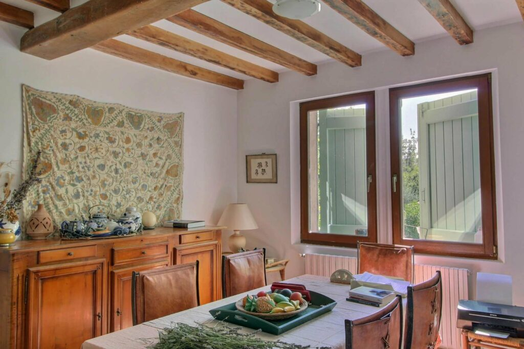 charming kitchen with exposed wood beams and two large windows