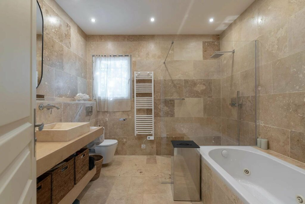 modern bathroom with tile walls and floros and white bathtub and small window