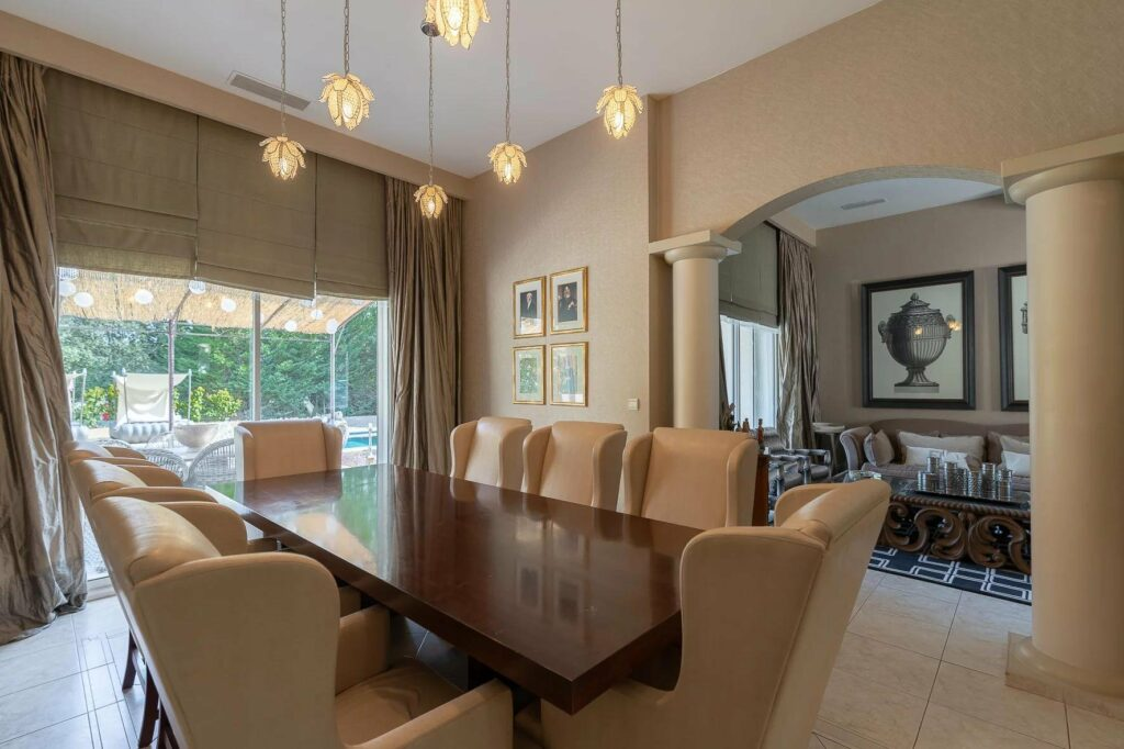 dining room of house with modern design and small round lights hanging above wood table