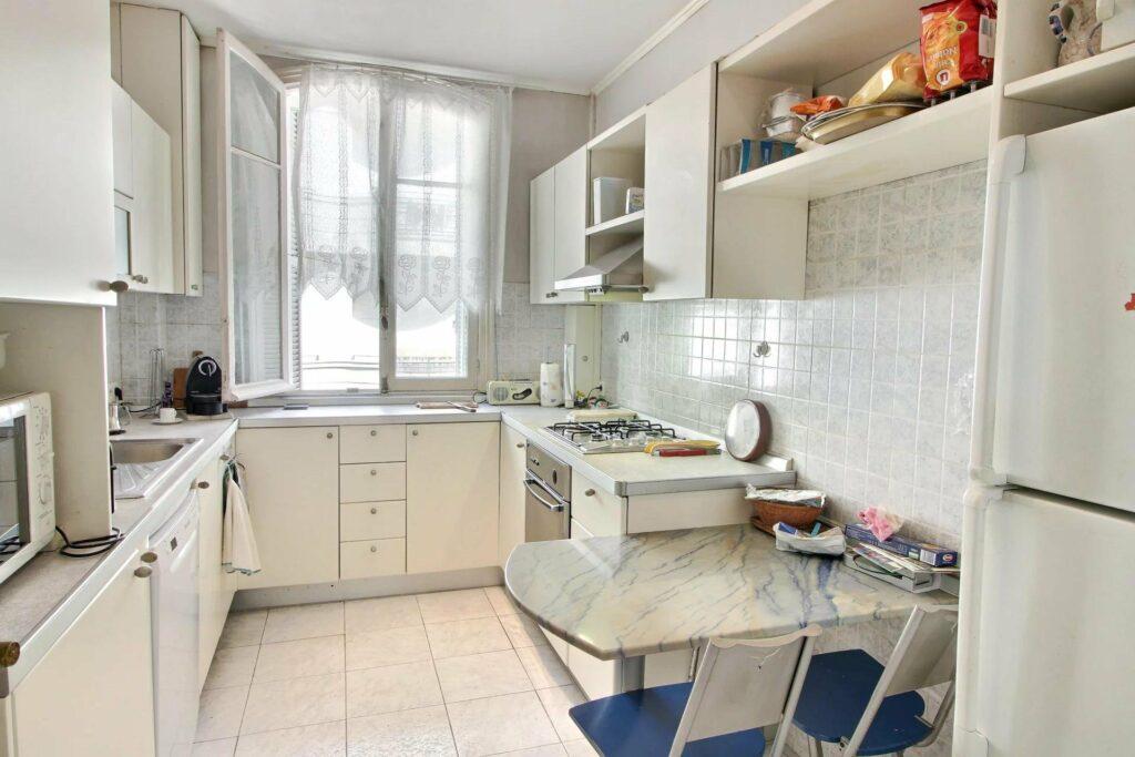 white kitchen white light tile floors and large windows