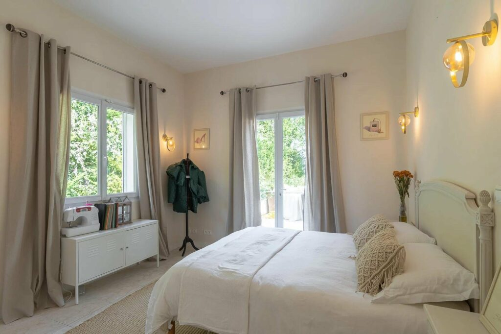 bedroom in draguignan villa with white walls and bed and small window next to bed