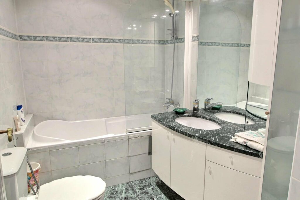 bathroom with white cabinets and dark marble counter top