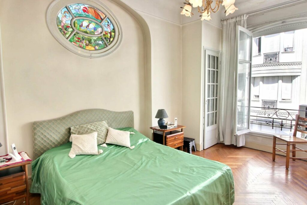 bedroom with green bedding and and white walls and small circular stained glass window