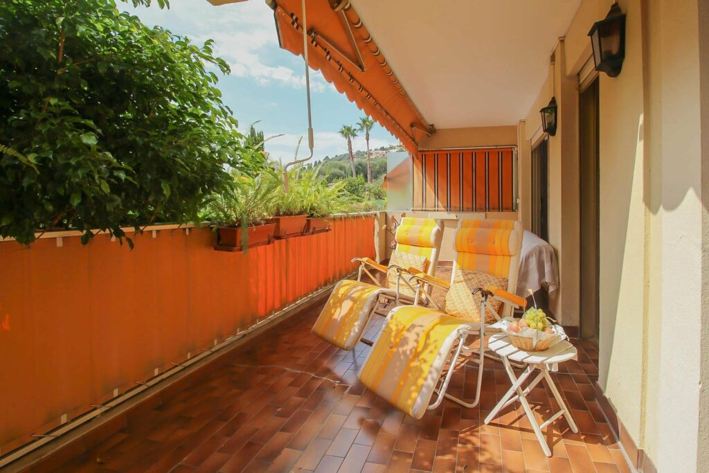 terrace with brown tile floors and yellow lay out chairs
