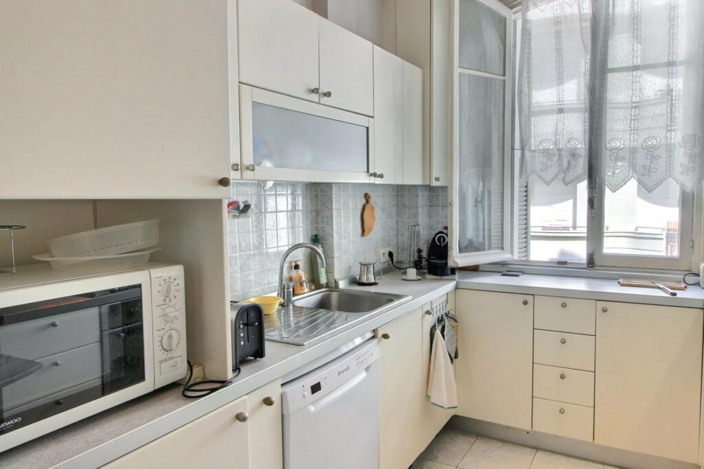 kitchen of apartment in nice promenade des anglais with white cabinets and white counter tops