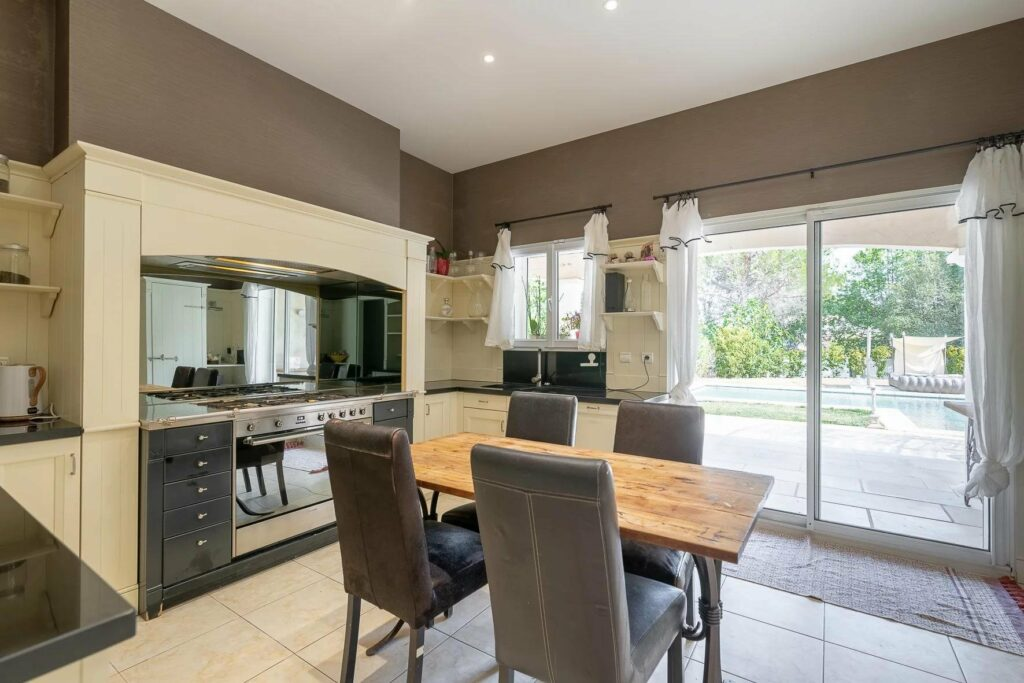 kitchen eating area with white tile floors and wood small table and view of kitchen