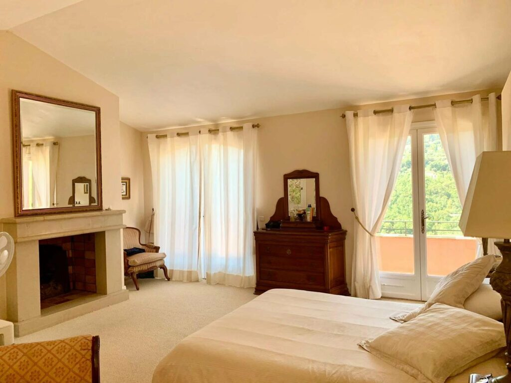 bright bedroom with white bedding and access to terrace