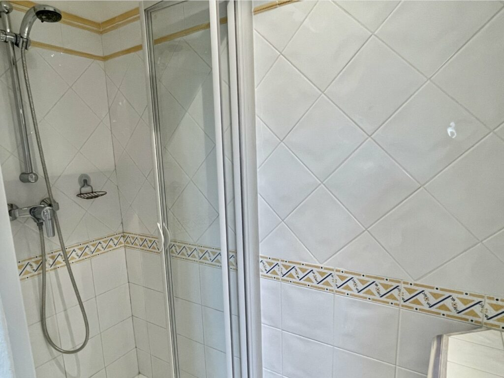 bathroom with white pattern tile walls in standing shower