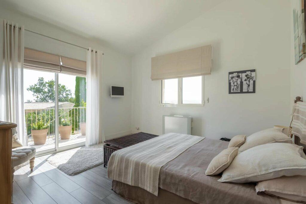 bedroom with white bed facing sliding door to backyard