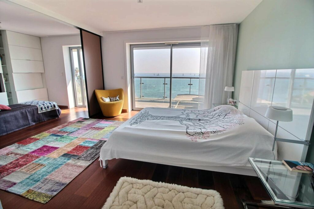 modern open bedroom with white bedding and terrace with sea view