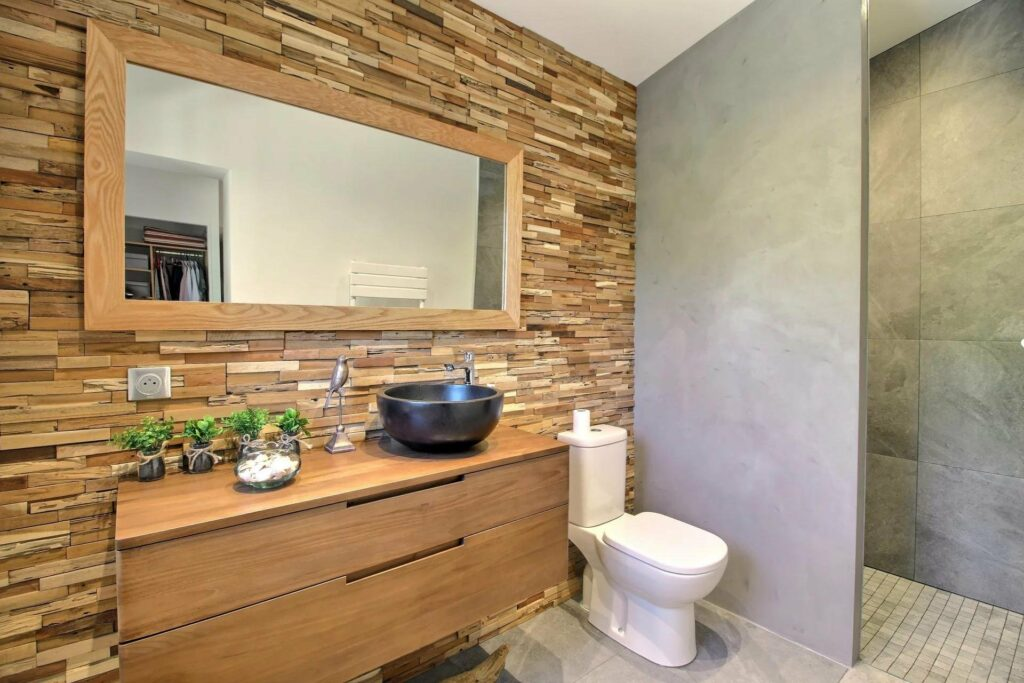 bathroom with stone wall design and wood cabinets