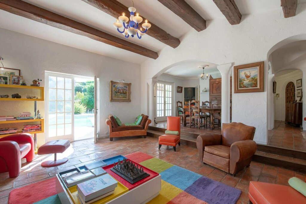 living room with colorful rug and exposed wood beams