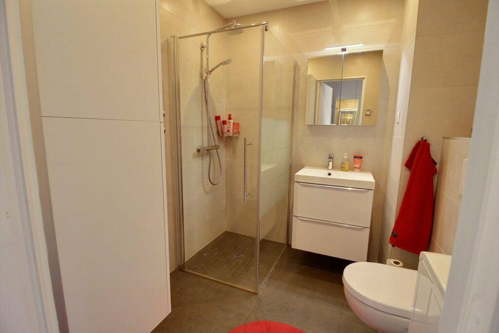 bathroom with grey tile floors and white sink and standing shower