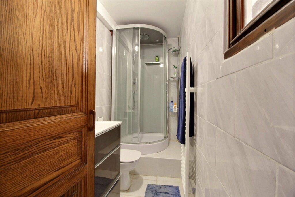 bathroom with white tile walls and floors and standing shower