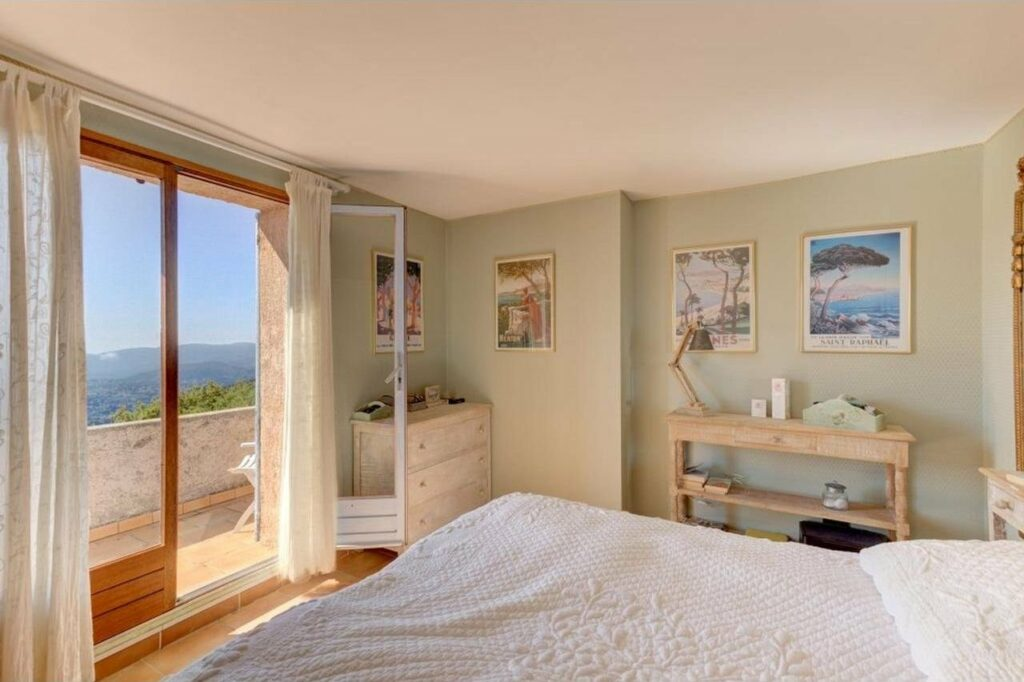 bedroom with white bedding and sliding door with ocean view