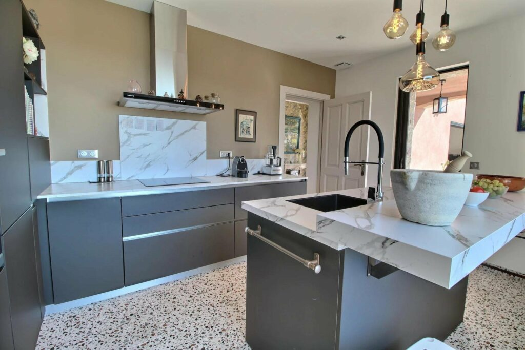 modern kitchen with grey cabinets and tile floors