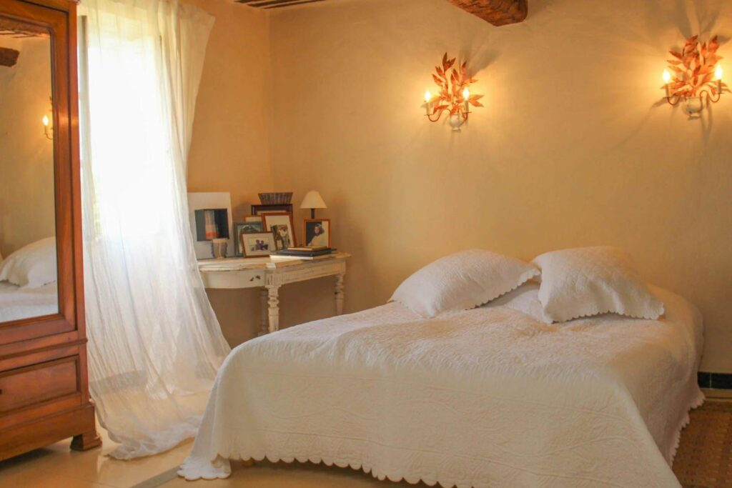 bedroom with white bedding and yellow wall in villa in fayence