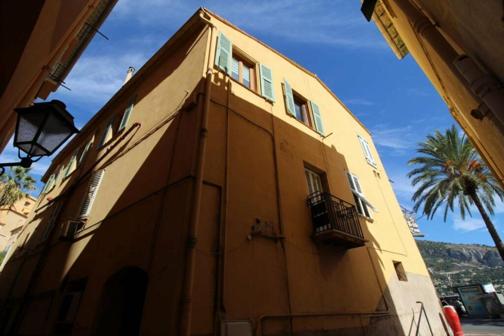 classic style apartment building in menton with light orange walls and blue shutters