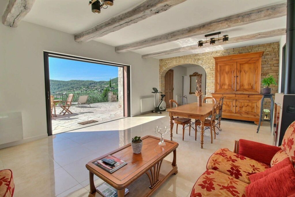 living room area of villa in seillans with tile floors and wood furniture