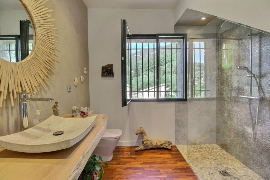 modern bathroom with wood floors and window view of mountains