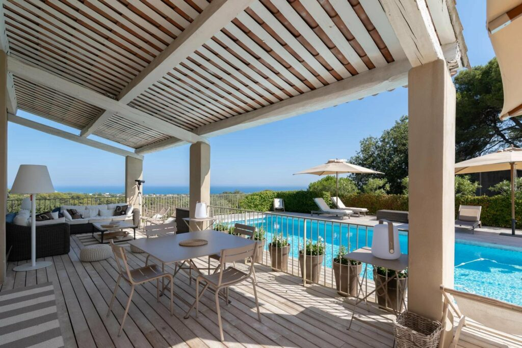 wooden deck area of biot villa with view of pool and sea