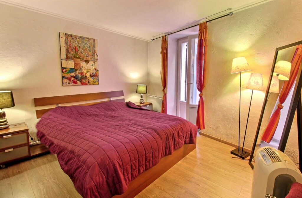 bedroom with dark red bedding and wood floors cannes