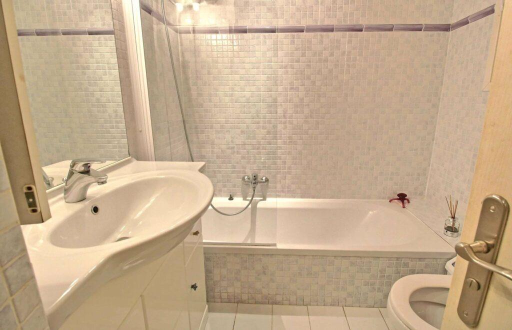 bathroom with white bathtub and light blue tile