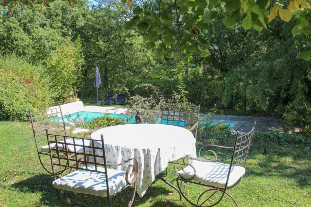 backyard of villa in south france with swimming pool and white table