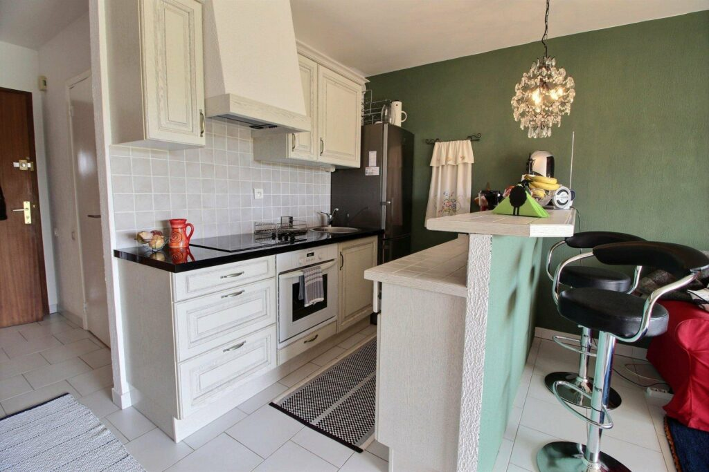 small kitchen with white cabinets at studio in antibes