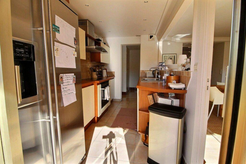 narrow kitchen with large steel fridge