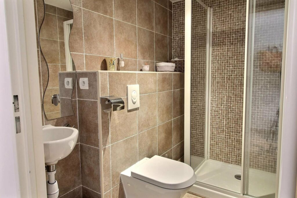 bathroom with beige tile walls and white standing shower
