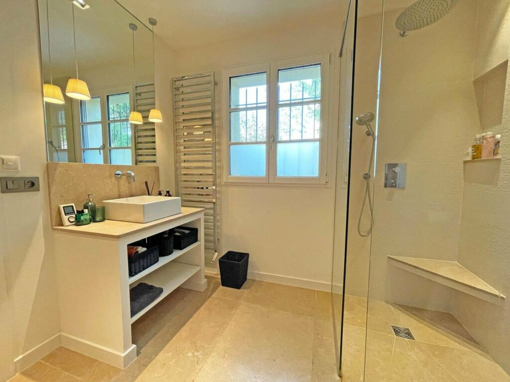 bathroom with large standing shower and white sink next to small window