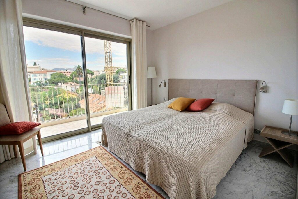 bedroom with large terrace and view of town
