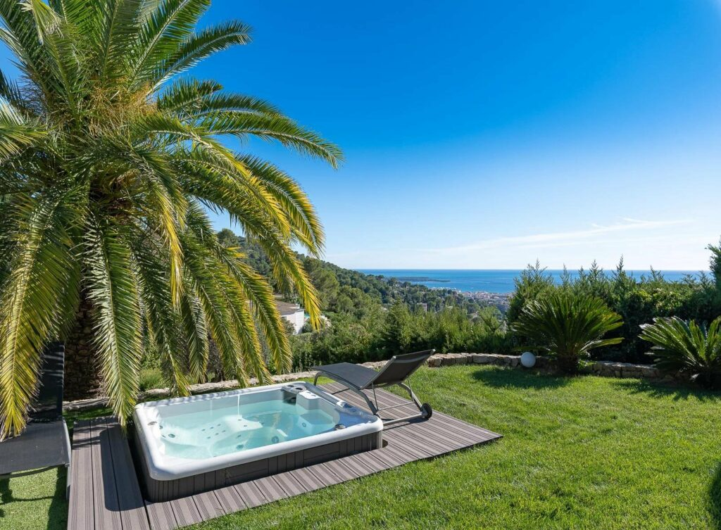 backyard with a jacuzzi and view of the mediterranean sea