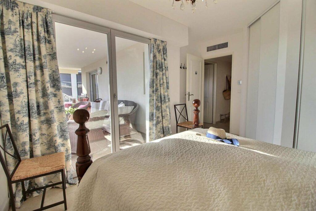 white bedding facing glass sliding door