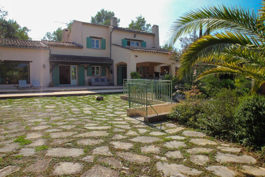 entrance of villa with stone floors and grass detailing