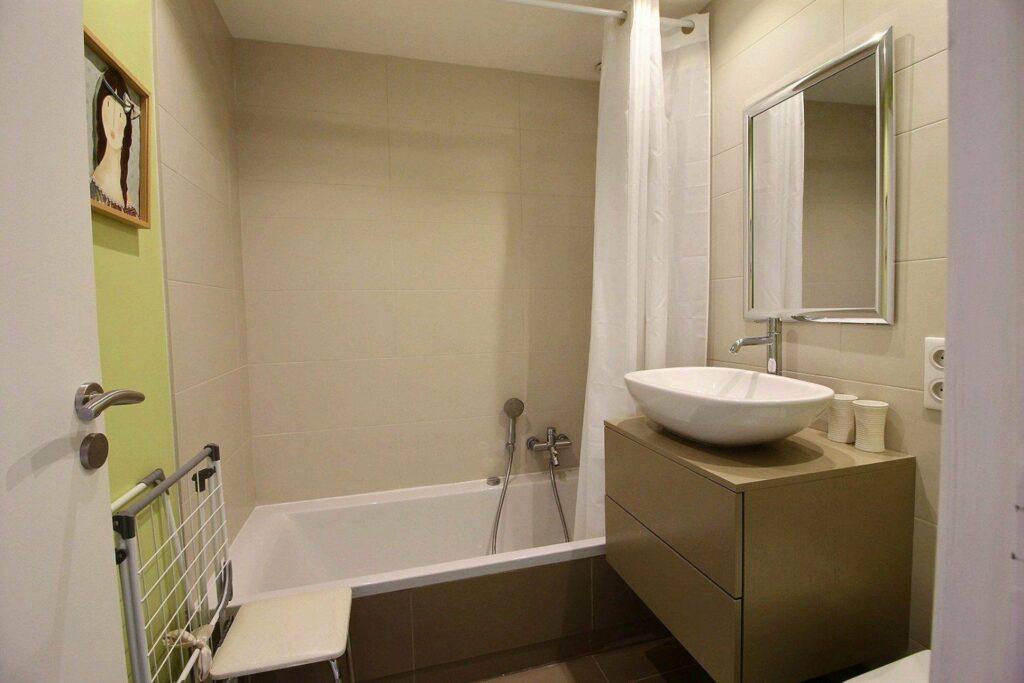 beige bathroom with white bathtub and modern design