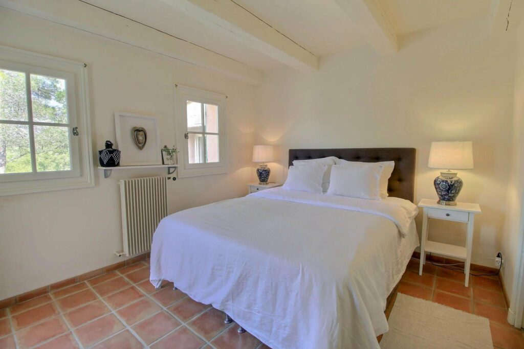 bright room of provencal villa with small window on side of bed