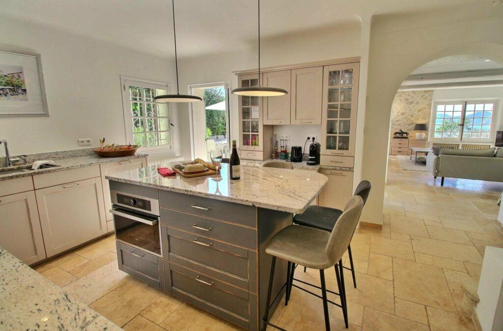 kitchen with dark brown island in center with overhead lights