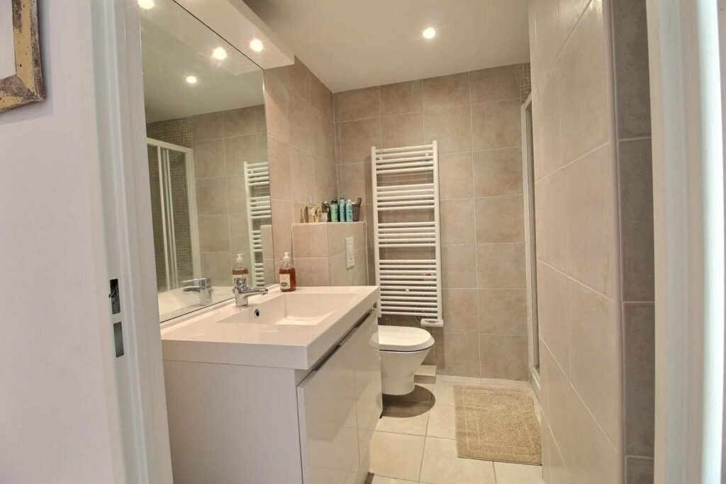 bathroom with large mirror and white sink