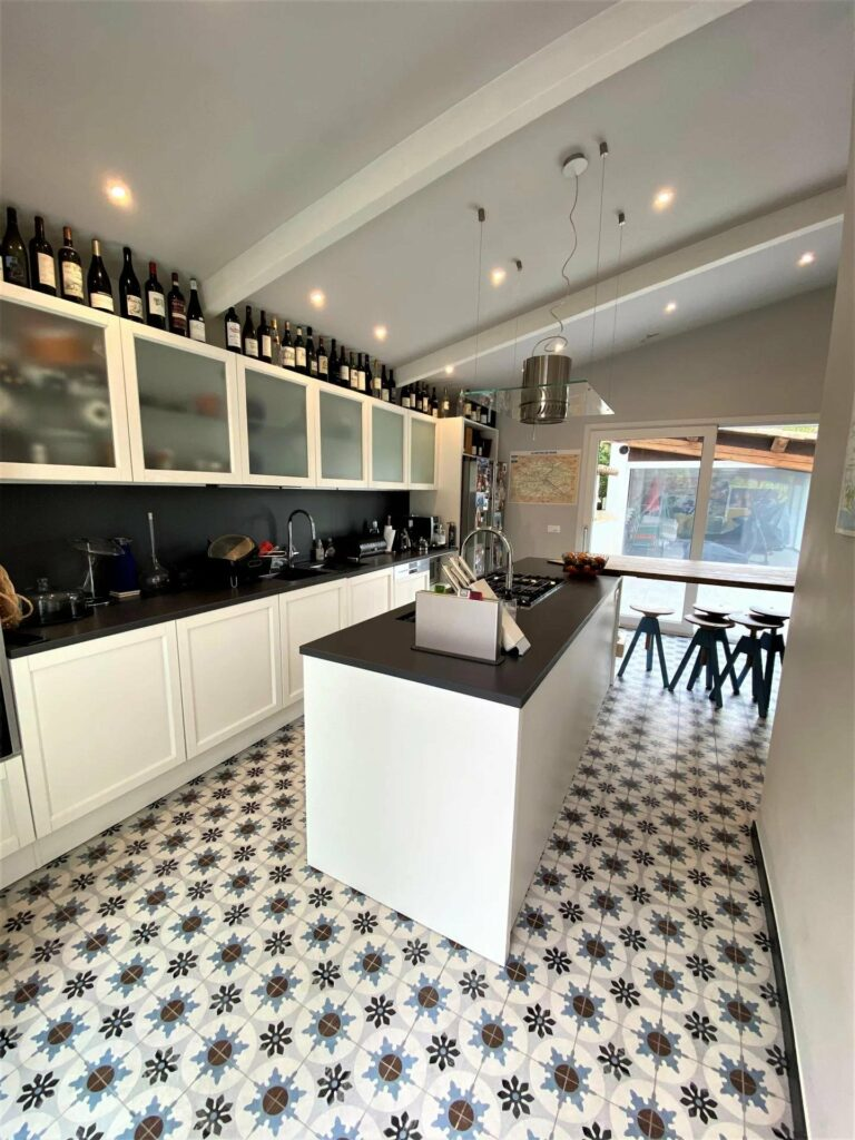 modern kitchen with black and white pattern floors and island in center