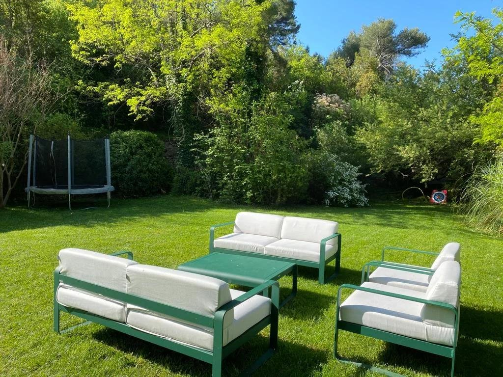 outdoor furniture in the middle of garden surrounded by trees