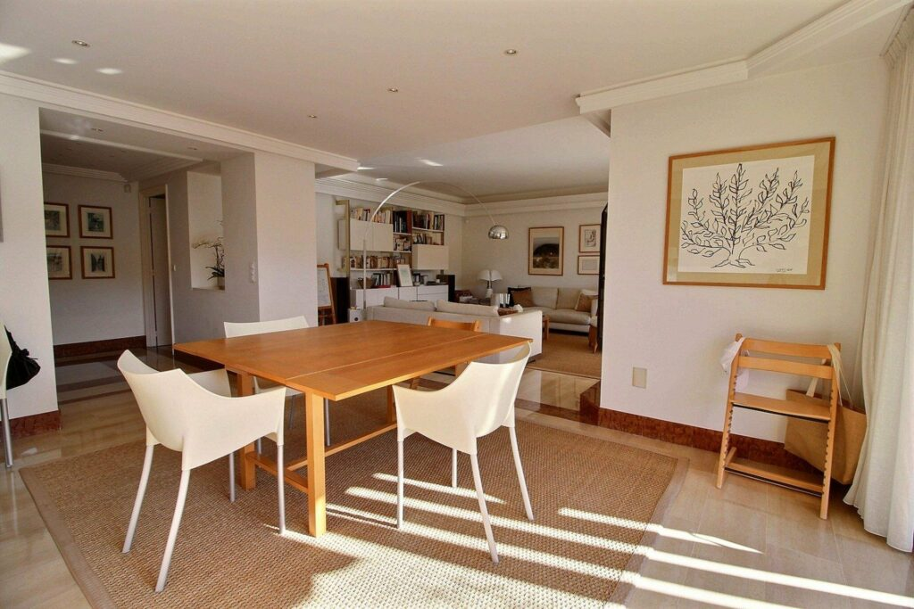 dining room with light wooden table with white chairs